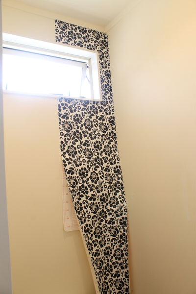 One strip of black and white wallpaper hanging down to the right of window