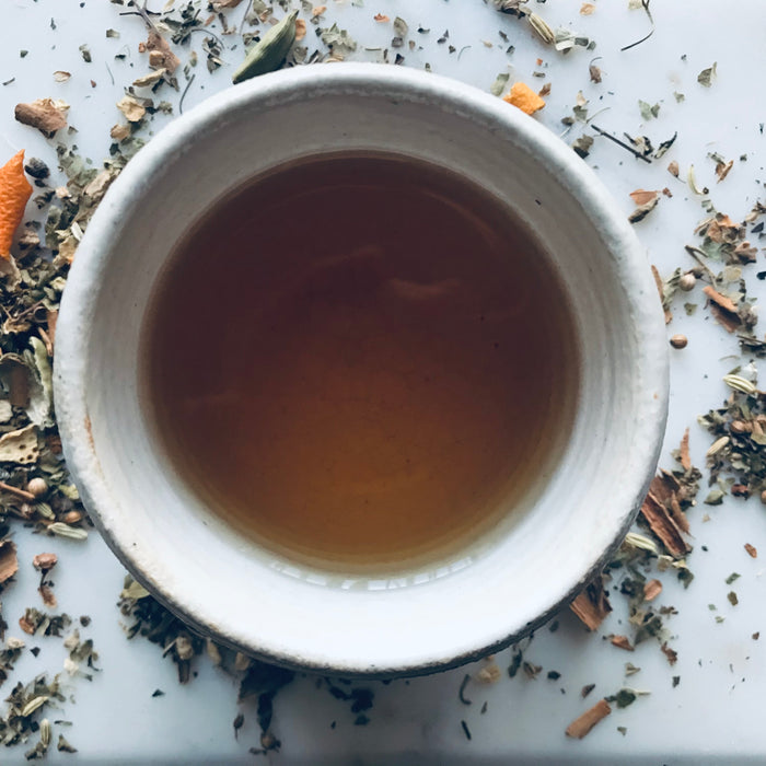 cup of tea with herbs around