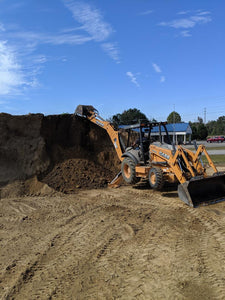 Backhoe preparing to load top soil at office site for Dodd Construction in Centre, Alabama