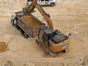 Dump truck parked in chert pit while being loaded by excavator with chert