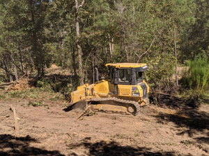 Bulldozer clearing trees and undergrowth on land in Cherokee County Alabama