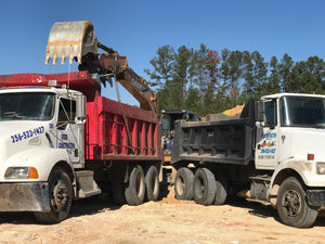 Two dump trucks being loaded with chert