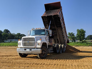 Dump truck delivering chert to new building pad in Centre, Alabama