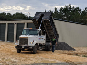 Dump truck delivering crusher run gravel to new storage building site in Centre, Alabama