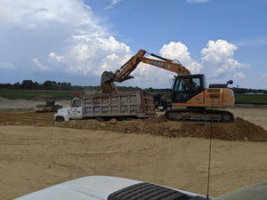 Excavator removing top soil from construction site of new Tractor Supply Company in Centre, Alabama
