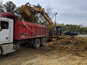 dump truck owned by Dodd Construction being loaded with dirt by excavator