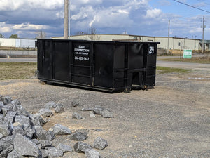 Black roll-off dumpster on construction job site