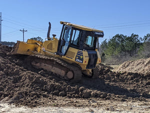 yellow Komatsu dozer pushing dirt up hill