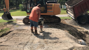 Chert and gravel being compacted during driveway repair by Dodd Construction in Centre, Alabama