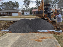 Load image into Gallery viewer, Crusher run gravel being spread by backhoe owned by Dodd Construction over new driveway tile