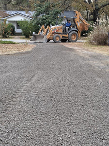 Backhoe spreading gravel on driveway for Dodd Construction customer in Centre, Alabama