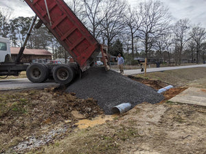 Gravel being dumped by Dodd Construction dump truck onto new driveway tile in Centre, Alabama