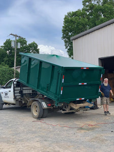 Rented construction dumpster being delivered to customer job site