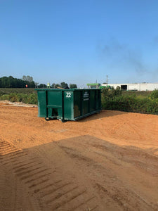 green metal rental dumpster on dirt construction job site in Centre, Alabama