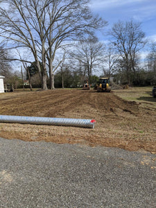 Driveway tile placed onto customer's land while waiting on dozer to remove top soil for new driveway installation