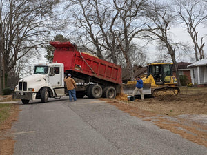 Dump truck delivering chert for new driveway tile in Centre, Alabama