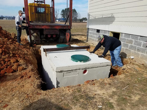 New septic tank being lowered into the ground by Dodd Construction in Centre, Alabama