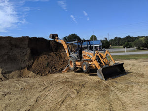 Preparing to load top soil pile onto dump truck for delivery