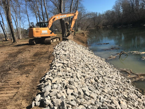 Rip rap being placed by excavator on bank of Weiss Lake in Centre, Alabama