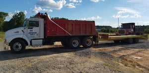 Dump truck and equipment hauling trailer parked at office of Dodd Construction in Centre, Alabama