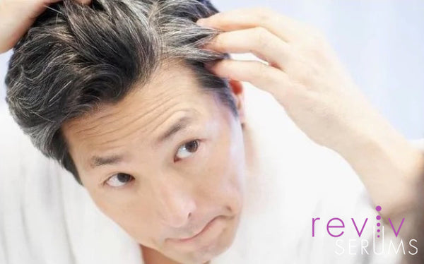 Asian man examining premature greying hair