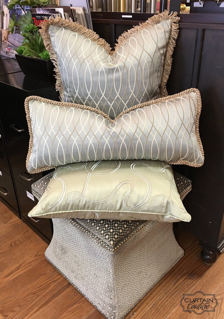 Pillows on top of Upholstered ottoman by Curtain Couture