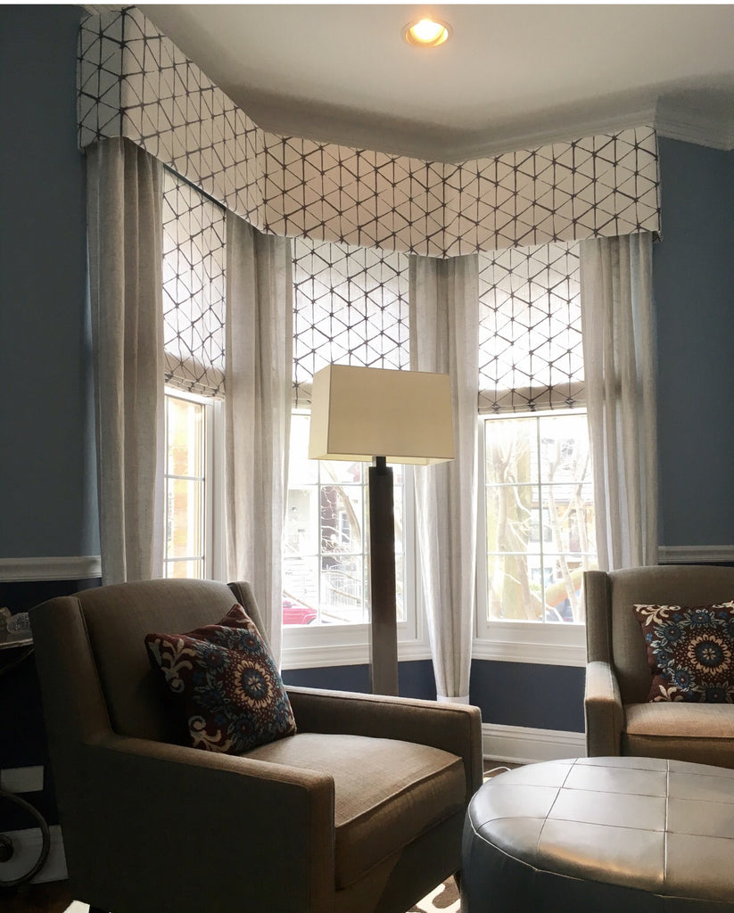 Contemporary geometric flat roman shades with matching cornices, completed with stationary panels. This creates a soft surrounding with enough sunlight filtered through.