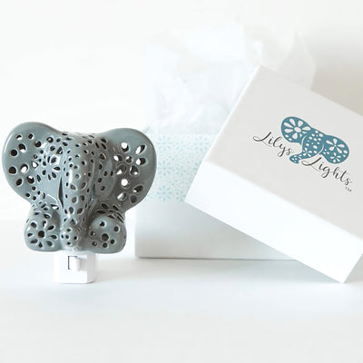 Hand crafted grey elephant night light sitting on a white table with Lily's Lights gift wrap packaging in the background.