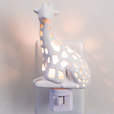 White hand carved giraffe night light plugged into an outlet and switched on.