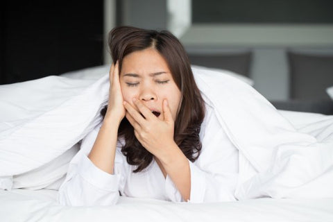 Woman who is yawning because she isn't getting the required Sleep
