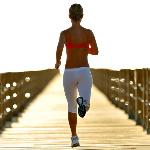 A tanned slim lady with white jogging bottoms and pink sports bra running on a wooden pier