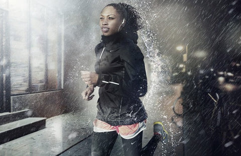 a woman wearing a tracksuit running in the rain