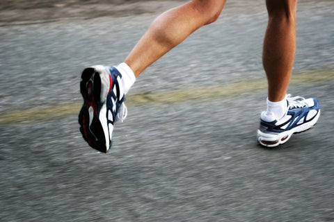 action shot of a persons legs running on tarmac