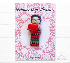 Guatemalan worry doll holding a red heart