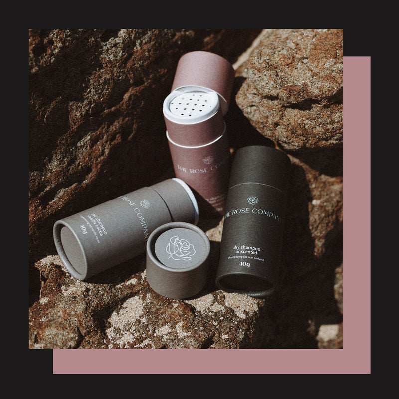 The Rose Company Vegan Dry Shampoo in three scents: Rosemary Bergamot, Vanilla Cocoa, Unscented in compostable sustainable paper tube packaging.