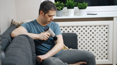 Man sitting on couch using vybe massage gun