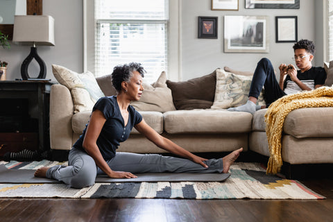 A mom stretches after using Vybe Massage Gun to ease sore muscles.
