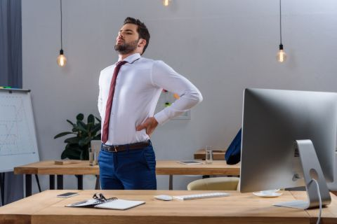 Man standing at desk stretching tight back.
