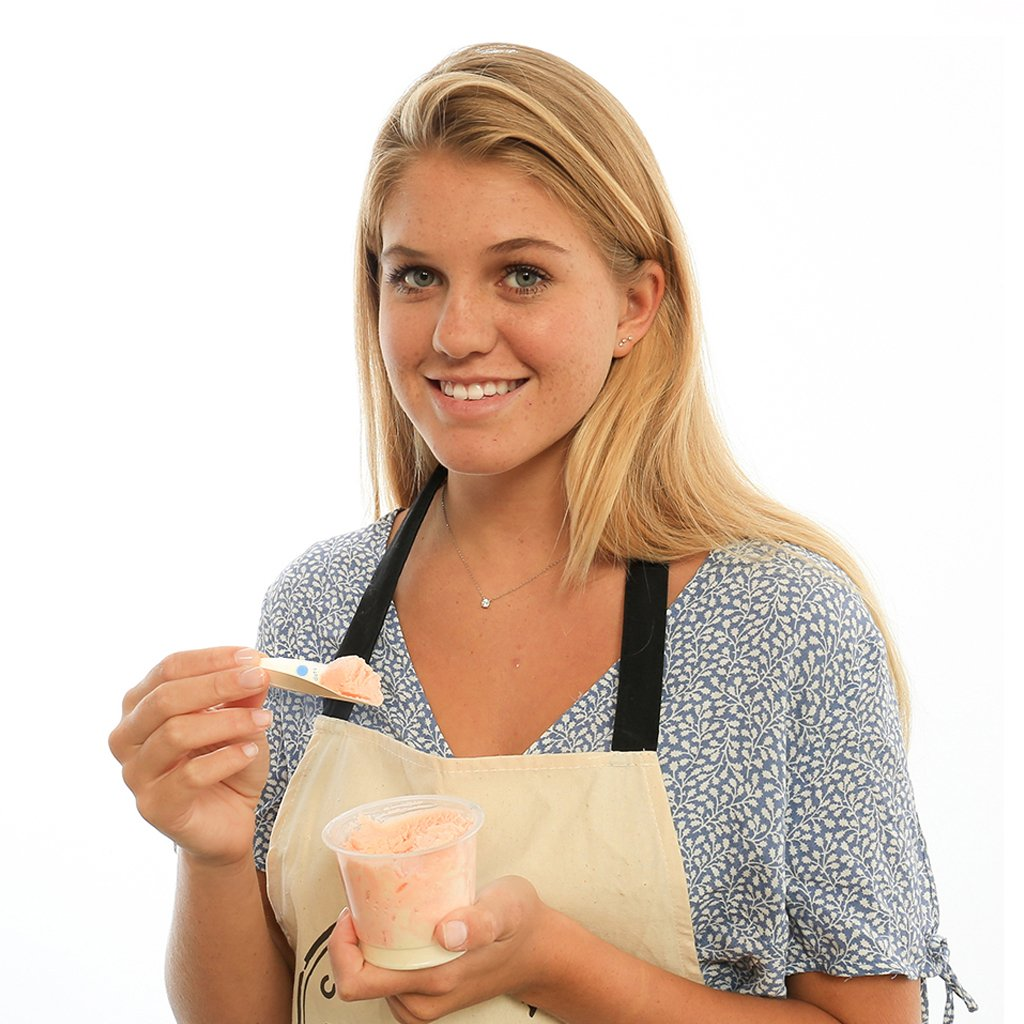 Young woman eating a cup of ice cream using the EcoSpoon 4, a biodegradable utensil that tastes better than wood.