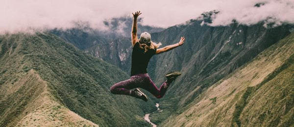 Darvaza Teas Explore Caffeine in Tea Woman jumping in front of mountains