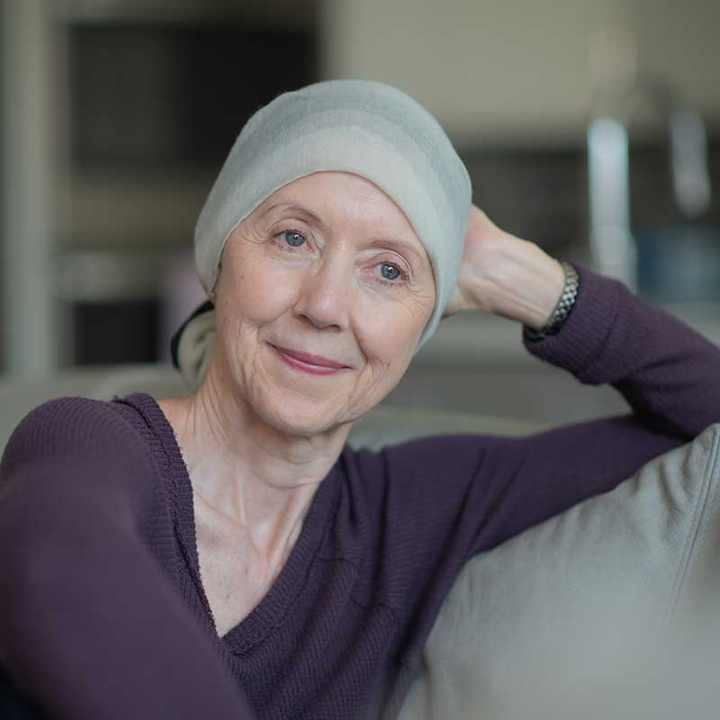 An older woman with a scarf wrapped around her head sitting on the couch. Learn more about ovarian cancer awareness.