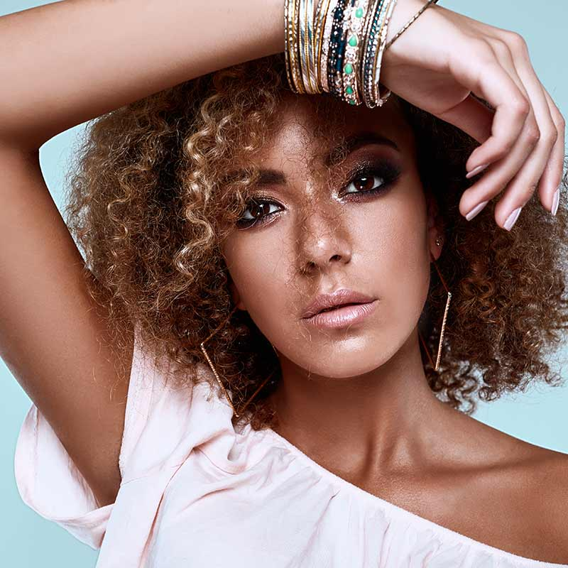 Boho beauty look elegant Black woman with curly hair. Find out which clean beauty products to use for a beachy boho vibe at Solstice Sol's blog.