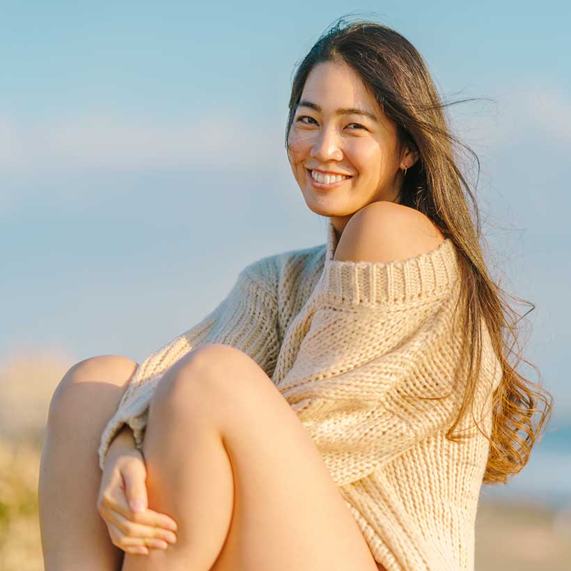 A young woman wearing a sweater sitting on the beach. Discover 5 fun clean skincare trends for 2021.
