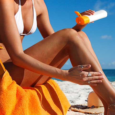 A woman applies sunscreen to her legs on the beach. Learn more about this and other clean beauty products.