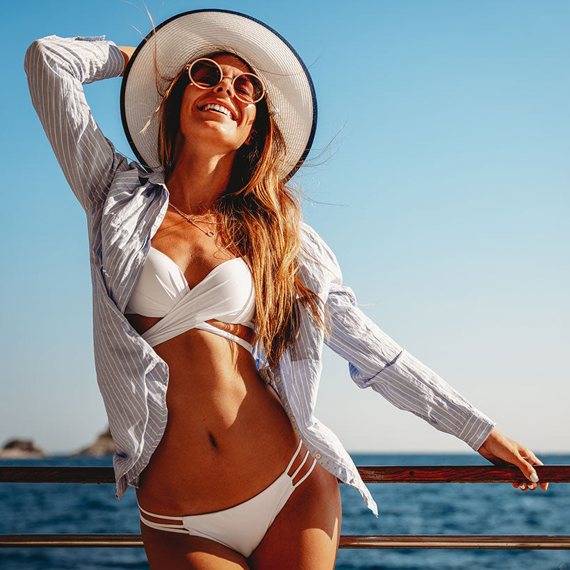Happy woman in bikini and sunhat protecting her skin from skin cancer with sunless tanner.