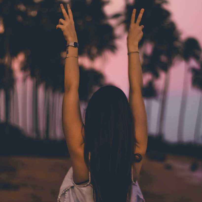 A tan woman facing away from the camera, holding two hands with peace signs up in the air. Discover the secret of how to get glowing skin.