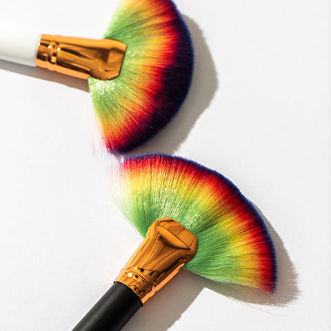 Two rainbow fan brushes, one with a black handle and one with a white handle.