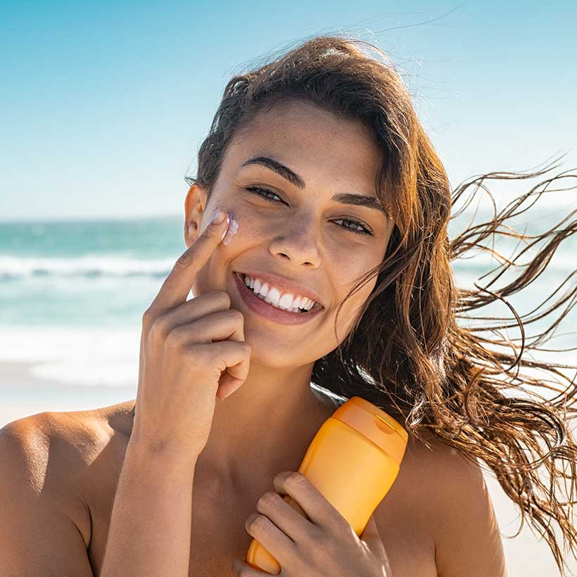 Image of a healthy young woman on the beach applying lotion to her face. Discover the surprising truth about the chemicals lurking in your favorite beauty products.