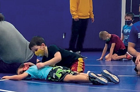 Calahan Cornelius, age 5, (putting in a half-nelson) and Maxwell Schmitz, 6, are learning the sport at wrestling club in Bellevue, Iowa.