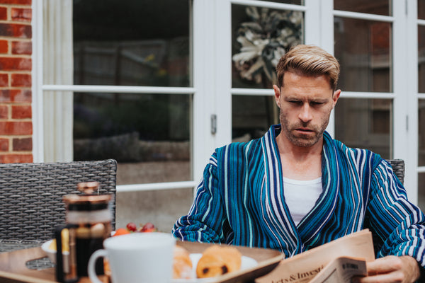 man reading newspaper in dressing gown